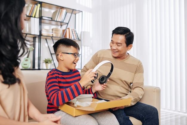 Opgewonden blije preteen vietnamese jongen die een koptelefoon uit de geschenkdoos haalt die zijn ouders hem hebben gegeven