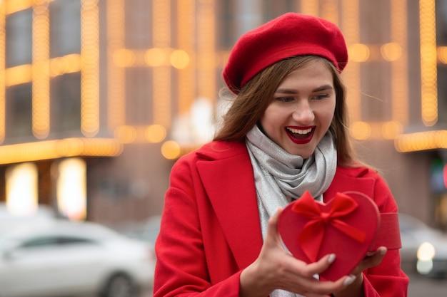 Opgewonden blonde vrouw draagt een rode baret en een jas die een hartvormige geschenkdoos opent op de achtergrond van bokehlichten. ruimte voor tekst