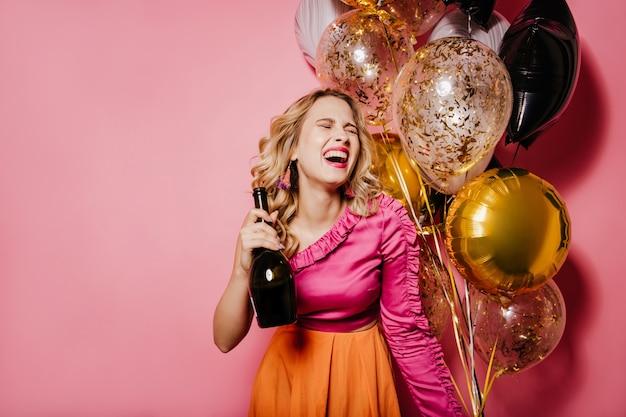 Opgewonden blonde vrouw met champagne die op roze muur lacht