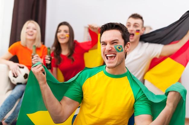 Opgewonden braziliaanse man met haar vrienden juichen voetbalwedstrijd