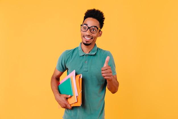 Opgewonden bruinharige man in glazen met boeken. zorgeloze afrikaanse student geïsoleerd.
