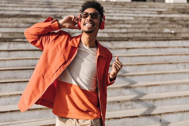 Opgewonden brunet charmante man in oranje jas, kleurrijk t-shirt en zonnebril zingt, glimlacht oprecht en luistert naar muziek in een koptelefoon buiten