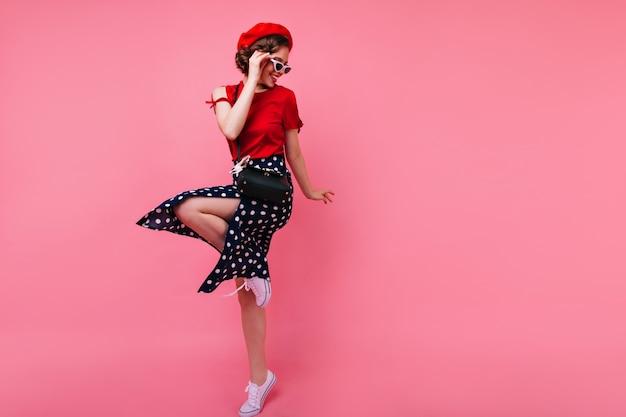 Opgewonden brunette dame in zwarte rok dansen op roze muur. aantrekkelijk wit meisje in het franse baret springen.