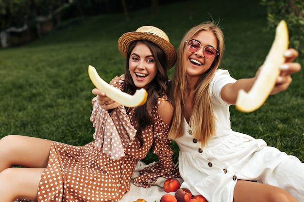 Opgewonden brunette en blonde vrouwen in stijlvolle zomerjurken glimlachen en houden stukjes meloen vast