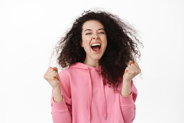 Opgewonden brunette vrouw winnaar, doel of succes bereiken, schreeuwen van vreugde en plezier, prijs winnen, overwinning vieren met opgeluchte gezichtsuitdrukking op wit