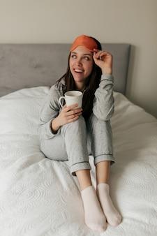 Opgewonden charmant meisje in pyjama en slaapmasker werd wakker, zittend op de badkuip met een kopje koffie in de ochtend. fijne dag thuis.