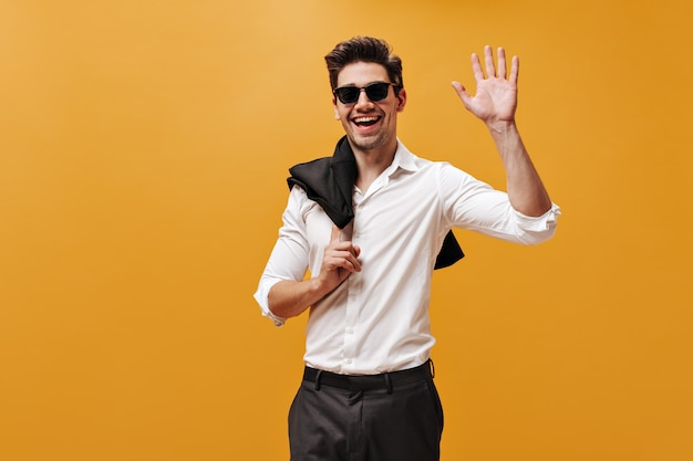 Opgewonden charmante brunet man in wit overhemd, zonnebril en zwarte broek glimlacht, houdt jas vast en zwaait hand in begroeting op oranje muur.