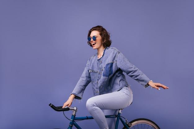 Opgewonden charmante vrouw die zich voordeed op de fiets. binnenfoto van overweldigende vrouwelijke geïsoleerde fietser.