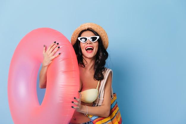 Opgewonden dame die in zonnebril zwemmende cirkel houdt
