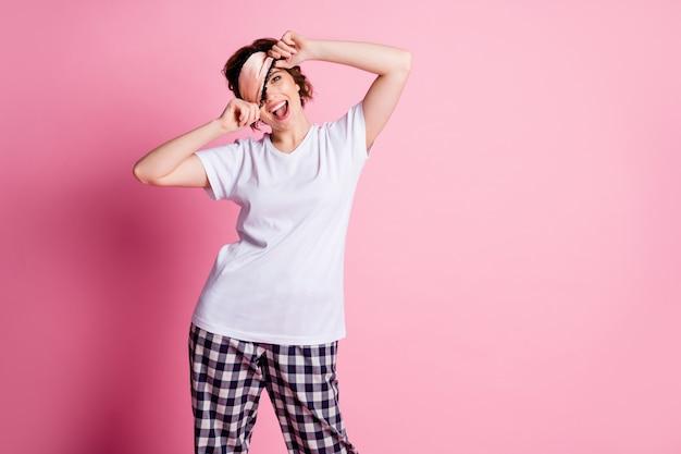 Opgewonden dame zijdeachtig slaapmasker opstijgen op roze kleur achtergrond