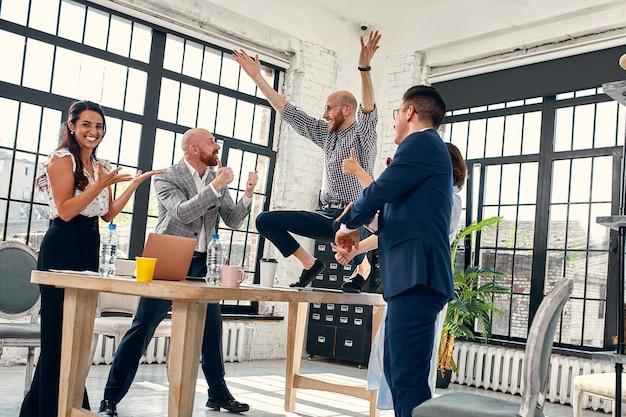 Opgewonden diverse zakelijke teammedewerkers schreeuwend vierend goed nieuws zaken winnen zakelijk succes, gelukkige multi-etnische collega-werknemersgroep voelt zich gemotiveerd extatisch over geweldige prestatie.