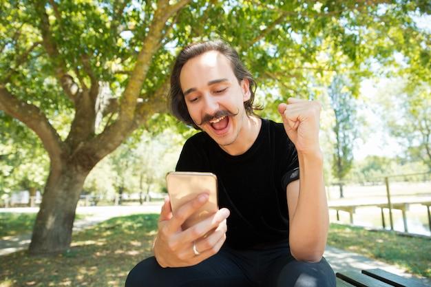 Opgewonden dolblij man met smartphone verheugt zich over goed nieuws