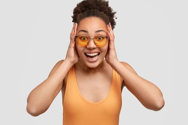 Opgewonden dolgelukkig meisje met een donkere huidskleur houdt beide handpalmen op het hoofd