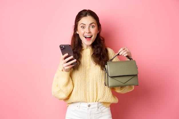 Opgewonden donkerbruin meisje bestelde portemonnee in online winkel, met smartphone, toont haar nieuwe tas en lacht verbaasd, staande over roze muur