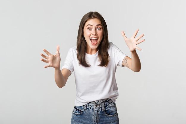 Opgewonden donkerbruin meisje dat verbaasd glimlacht en handen opheft om iets te vangen.