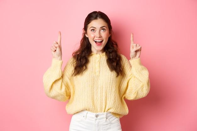 Opgewonden donkerbruin meisje dat vingers richt en met opgewekt gezicht omhoog kijkt, promotietekst leest, advertentie bekijkt, die tegen roze muur staat.
