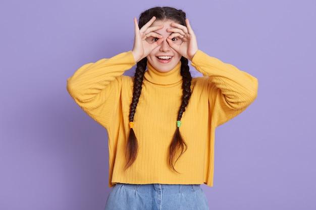 Opgewonden donkerbruine jonge vrouw met twee vlechten die zich met gelukkige uitdrukking bevinden en haar ogen behandelen met ok tekens