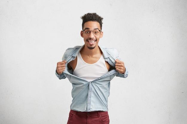 Opgewonden, donkere man met een specifiek uiterlijk scheurt het shirt van plezier af, adverteert met een nieuw t-shirt.