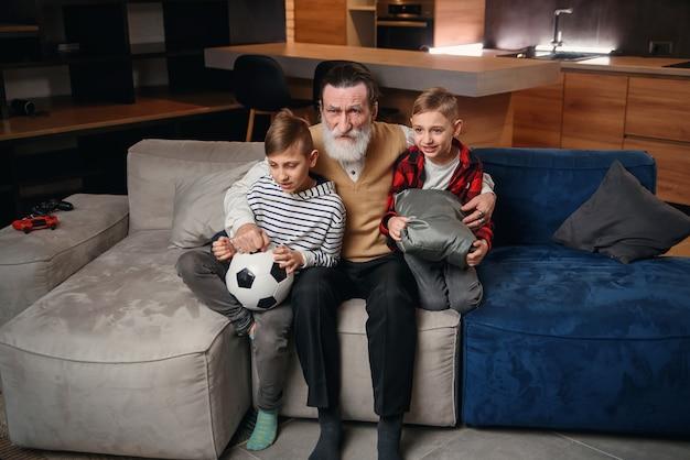 Opgewonden drie generaties mannen, sportfans ontspannen in de woonkamer, vieren samen de teamoverwinning, dolblije kleine jongen met vader en grootvader veel plezier samen voetbalwedstrijd thuis kijken