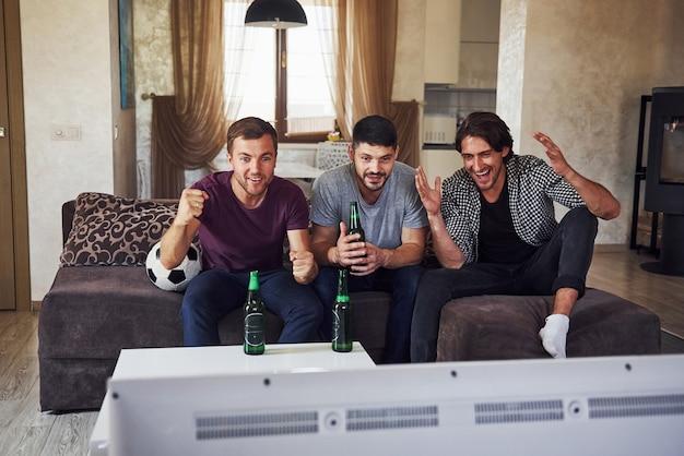 Opgewonden drie vrienden die samen thuis voetbal kijken op tv.