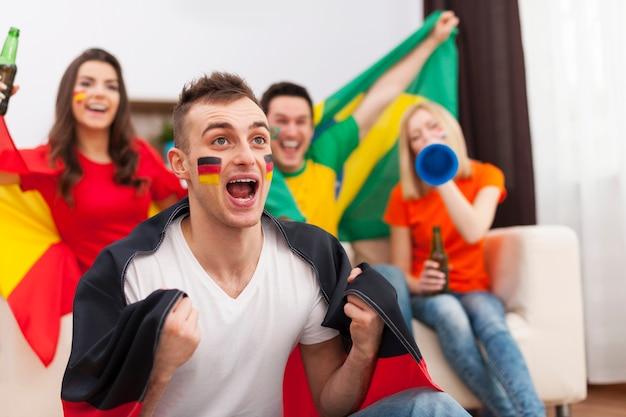 Opgewonden duitse man met haar vrienden juichen voetbalwedstrijd