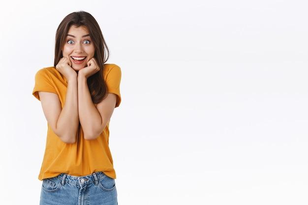 Opgewonden, dwaze gefascineerde jonge vrouw is dol op het zien van geweldige trailers met favoriete acteurs, hand in hand op kaaklijn en wangen samenknijpen opgewonden, glimlachend verbaasd, staande verbaasde witte achtergrond