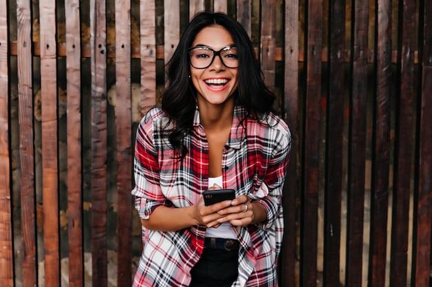 Opgewonden elegant meisje in de lente-uitrusting die op houten muur lacht. buiten schot van geweldige latijns-vrouw in glazen met telefoon met glimlach.