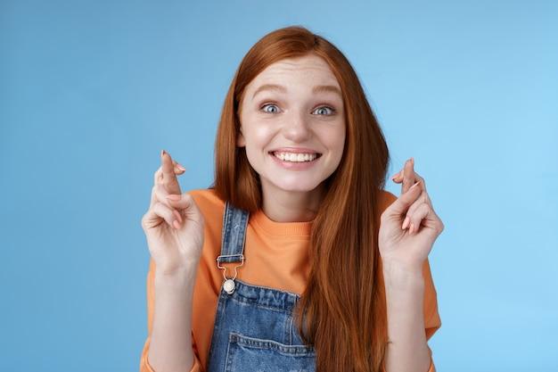 Opgewonden emotioneel gelukkig vrolijk roodharige meisje glimlachen optimistisch staren verrast opgewonden kruis vingers veel geluk geloven droom uitkomen wensen alleen vooruitziende goed nieuws blauwe achtergrond