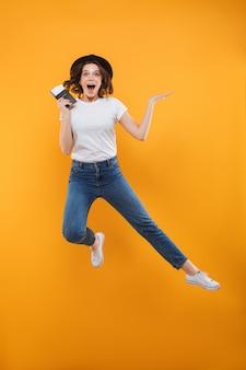 Opgewonden emotionele jonge vrouw toerist geïsoleerd springen