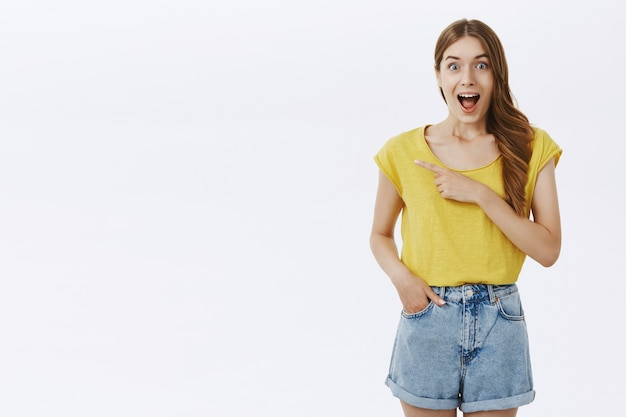Opgewonden en geamuseerd mooi meisje dat geweldig nieuws aankondigt, wijzende vinger verbaasd achtergelaten