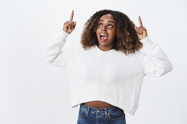 Opgewonden en geamuseerde afro-amerikaanse vrouw met krullend haar in wintertrui schreeuwend van verbazing en verrassing kijkend en wijzend verbaasd reagerend op coole promotie over witte muur