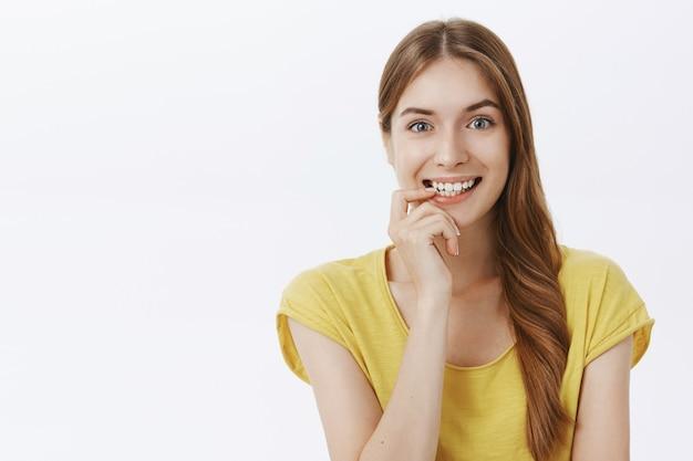 Opgewonden en geïntrigeerd lachend meisje in de verleiding om iets interessants te proberen en er attent uit te zien