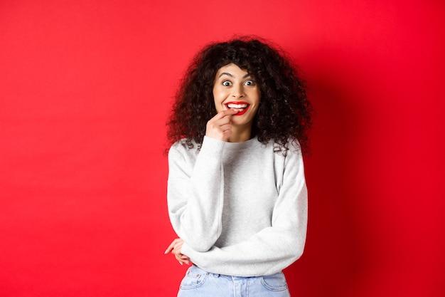 Opgewonden en geïntrigeerde vrouw die graag iets probeert, verleid kijkt en geamuseerd vingernagel bijt, staande over rode achtergrond.