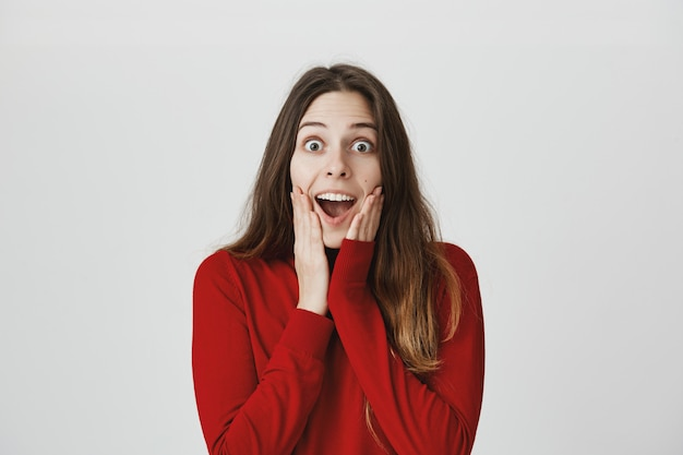 Opgewonden en gelukkig aantrekkelijke vrouw, open mond horen prachtig nieuws