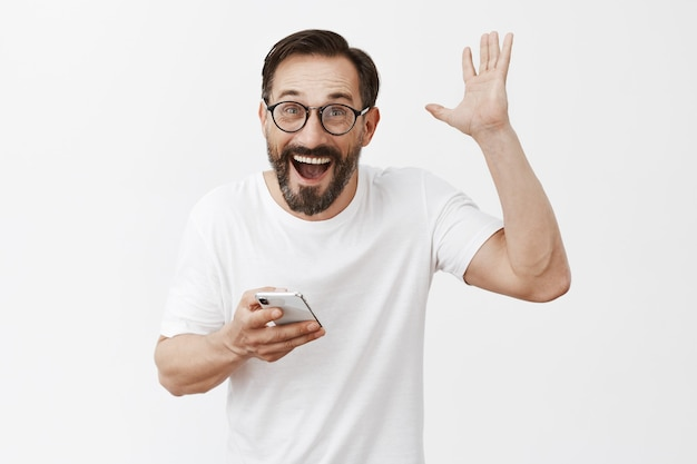 Opgewonden en gelukkig bebaarde volwassen man poseren met zijn telefoon