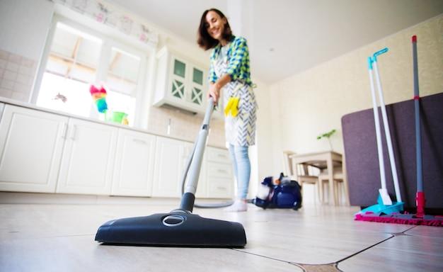 Opgewonden en gelukkig mooie jonge vrouw in een schort is het schoonmaken van de vloer in haar keuken thuis en dansen