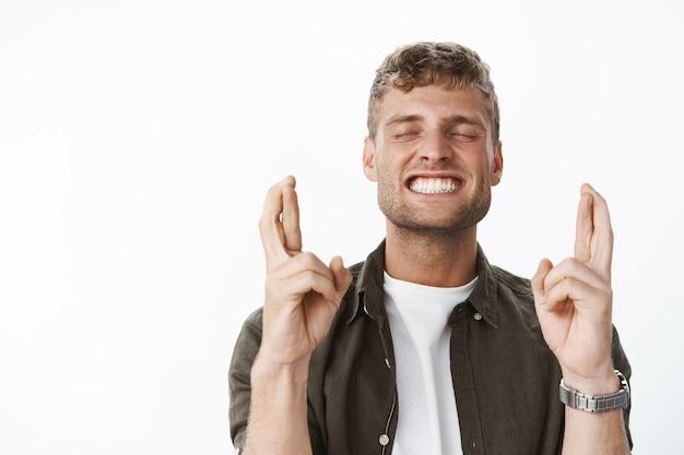 Opgewonden en gelukkige aantrekkelijke blonde man met borstelige ogen dicht opgewonden en glimlachend opgetogen terwijl wachten op de droom eindelijk uitkwam, vingers kruisen voor geluk, hopelijk bidden