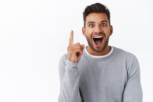 Opgewonden en gelukkige attente knappe man kreeg een uitstekend idee wat te kopen voor valentijnsdag, vond de perfecte variant in de winkel of winkelde online, steek de wijsvinger op in een eureka-gebaar, glimlachend verbaasd