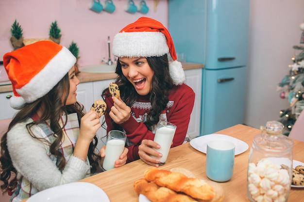Opgewonden en gelukkige jonge vrouw en meisje kijken elkaar aan en houden koekjes in handen. er zijn glazen melk in hun handen. mensen dragen leeshoeden. ze zitten in de keuken.