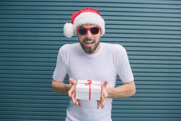 Opgewonden en geweldige man staat en kijkt ernaar uit. hij draagt een kerstmuts en een bril. ook man houdt aanwezig in handen. geïsoleerd op gestreept