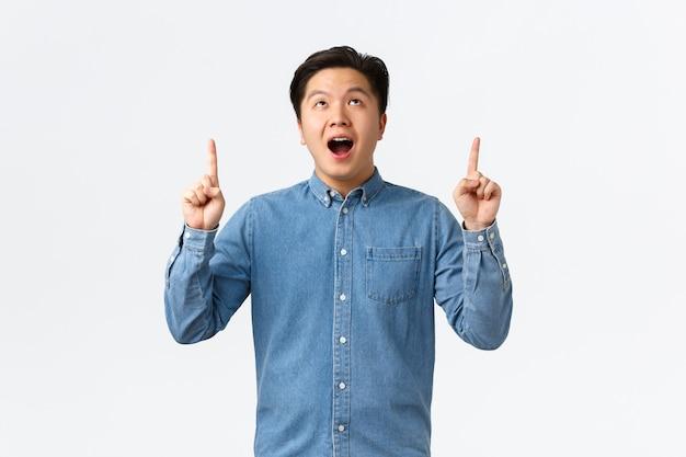 Opgewonden en onder de indruk aziatische jongeman opent zijn mond, zegt wow gefascineerd, bekijkt promo, kijkt en wijst met zijn vingers omhoog naar advertentie, staart naar geweldige banner, witte muur.