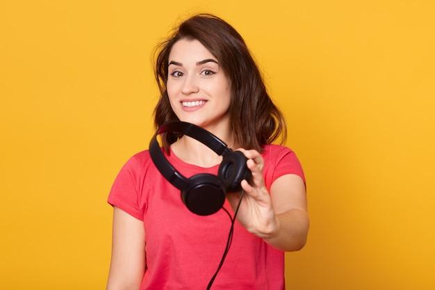 Opgewonden en onder de indruk vrouw met een brede glimlach, in een goed humeur, gekleed in een rood t-shirt