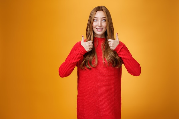 Opgewonden en ondersteunende roodharige vriendin die mening vraagt over nieuwe warme jurk die duimen omhoog laat zien en wenkbrauwen optrekt, ondervraagd als wachtend op mening over oranje achtergrond