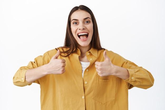 Opgewonden en ondersteunende vriendin toont duimen omhoog, blijf positief, wroeten, je kunt het gebaar doen, ga zo door, goed gedaan teken, tevreden tegen de witte muur staan