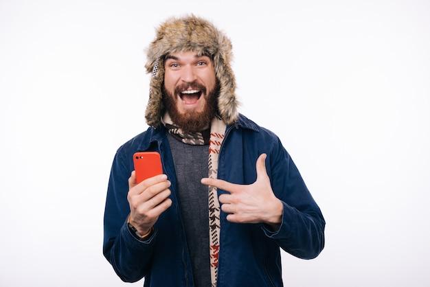 Opgewonden en verbaasd bebaarde hipster man in winterkleren wijzend op zijn smartphone
