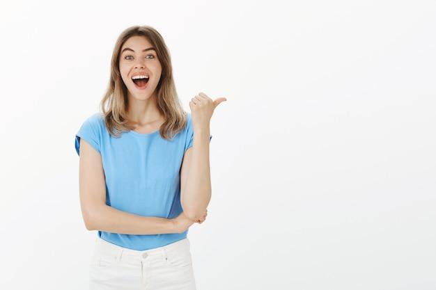Opgewonden en verbaasd blonde vrouw wijzende duim naar rechts, aankondiging tonen
