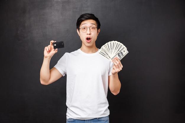 Opgewonden en verbaasd rijke gelukkige aziatische kerel met dollars en creditcard met verbaasde uitdrukking