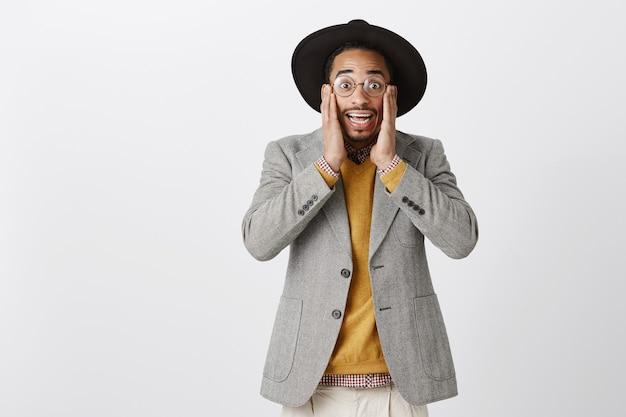 Opgewonden en verrast knappe afro-amerikaanse man kijkt opgewonden over fantastisch nieuws
