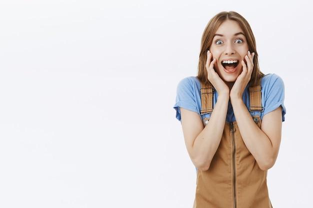 Opgewonden en verrast mooi meisje ziet een geweldig aanbod en reageert verbaasd en blij