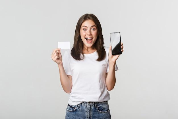 Opgewonden en verrast schattig meisje met creditcard en app voor mobiel bankieren op het scherm.